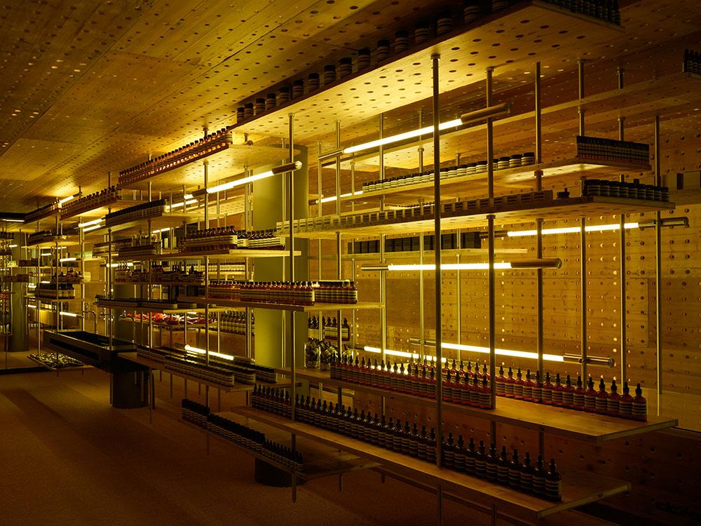 Rodney Eggleston a imaginé un environnement industriel pour la première boutique Aesop à Zurich (Oberdorfstrasse). L'espace étroit s'articule autour d'une étagère suspendue fabriquée à l'aide de matériaux recyclés des travaux publics, dont les planches jaunes d'échafaudages récupérées dans la ville.