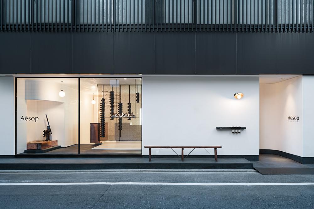 En noir et blanc, rehaussée d'accents de cuivre, la boutique de Kyoto créée par le bureau de Shinichiro Ogata, Simplicity, est empreinte de la culture japonaise du 14ème siècle à aujourd'hui. Des voiles en mailles noircies dans lesquelles sont cousues des bouteilles Aesop organisent l'espace dans sa verticalité comme autant de pages calligraphiées.