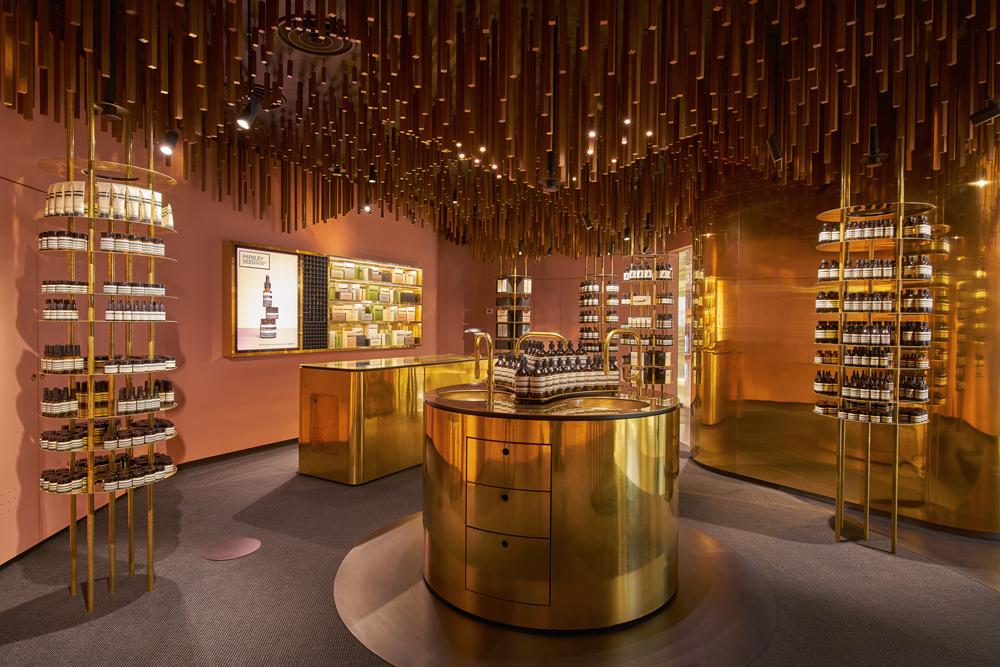 ION à Singapour est le quatrième projet réalisé par le bureau norvégien Snøhetta pour Aesop. Inaugurée en mai 2016, la luxueuse boutique en sous-sol rappelle le passé de plantation de muscade de Orchard Road. Si le laiton ou la teinte rosée des murs effleure l'histoire des lieux, le plafond se fait plus narratif et illustre les racines d'un verger au moyen d'une composition en bois.