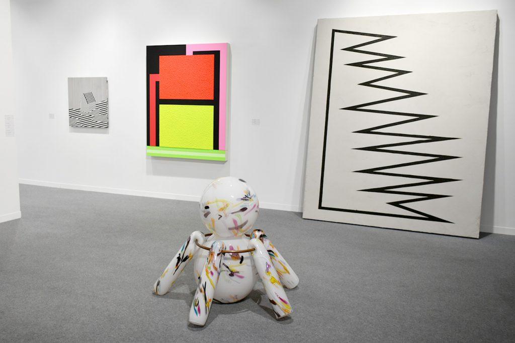 """La galerie Xippas de Genève avec au premier plan """"Feu d'artifice"""" en verre soufflé de Denis Savary et une oeuvre sur ciment d'Émilie Ding en arrière-plan."""